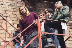 Photo of five young people hanging out on building fire escape