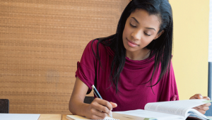 Photo of young female student writing in a notebook while sitting at a desk with a book